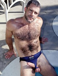 Hot bear gay Jeremy takes his erect dick out of his blue trunks and pumps it hard