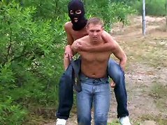Hunky ponyboy urged with the help of heavy belt carries his master on his back around a vast field