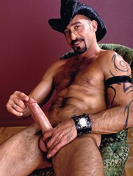 Husky looking gay wearing a cowboy hat and showing off his huge erect prick by rubbing it live