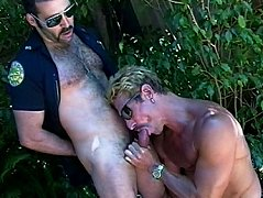Horny bear cop blows a blonde muscle head and gets sucked off while in the woods