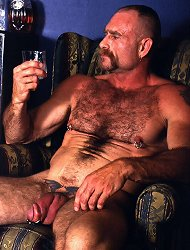 Tough looking gay bear sitting on a couch and playing with his shaft by rubbing it live