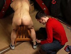 Horny master ties his slave on to a wooden rack and whips his shaven ass